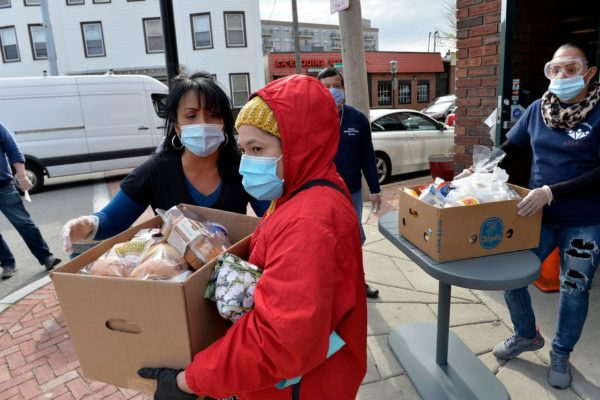 Gladys Vega, (left) Executive Director of the Chelsea Collaborative Inc. helps directing people in line in an effort to distribute food and packages of donated goods to people in need.