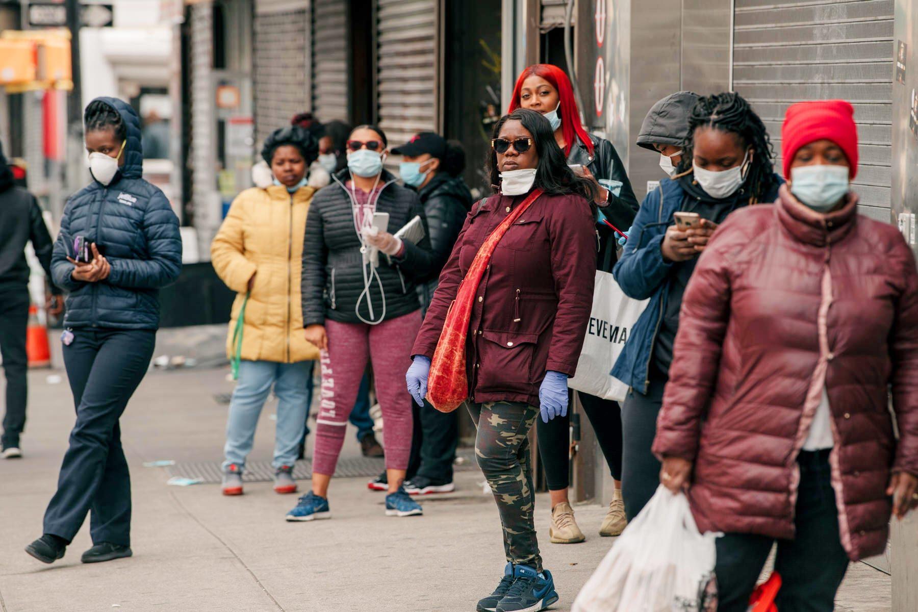 Pedestrians wear face masks on Fulton Street.