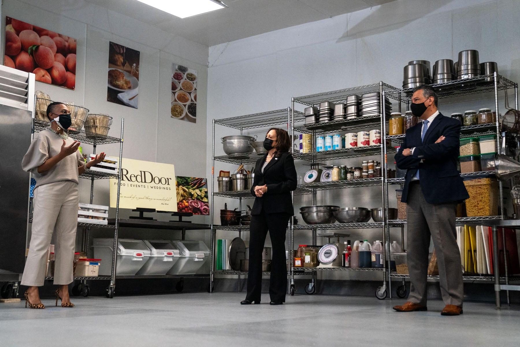 Reign Free, Owner of Red Door Catering speaks as Vice President Kamala Harris and Sen. Alex Padilla (D-CA) listen in the RedDoor kitchen.