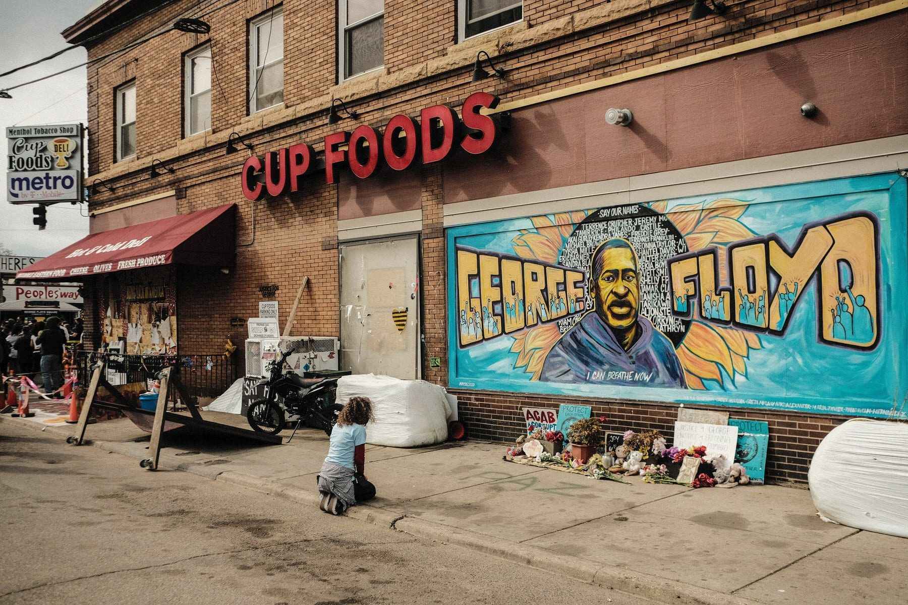 A woman pays respect to a mural of George Floyd by the Cup Foods storefront.