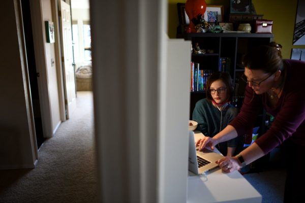 A mother helps her daughter with online classes in their home.