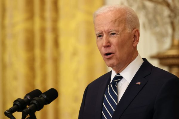 Joe Biden speaking at a dias into a microphone
