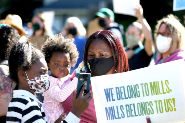 Skyler Mills, 10, left, Kinsey Mills, 2, and their mother Robin Mills, a Mills College alumna, hold up a sign during a rally at Mills College.
