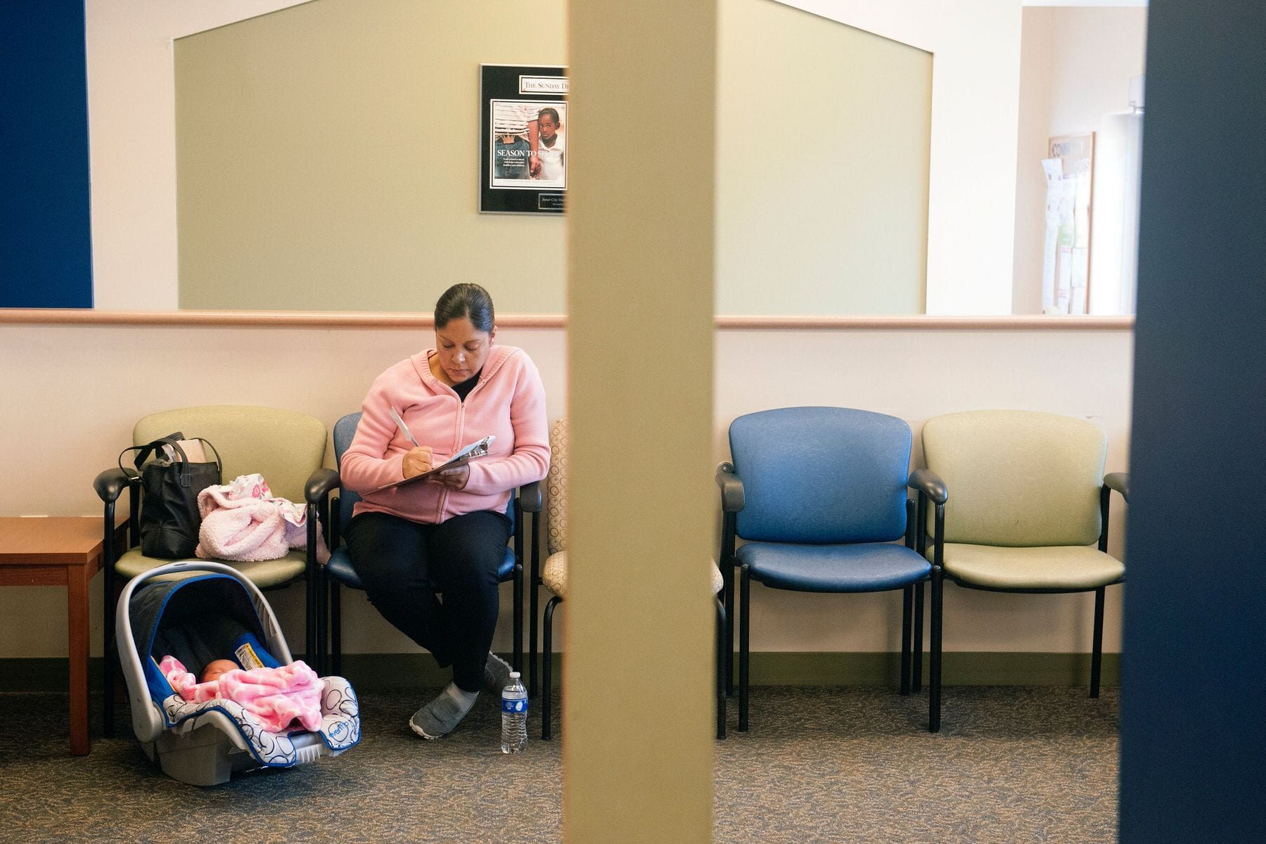 A woman fills out paperwork prior to a checkup with her 5-day old daughter.