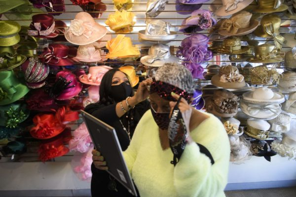 Woman helping another woman try on hats