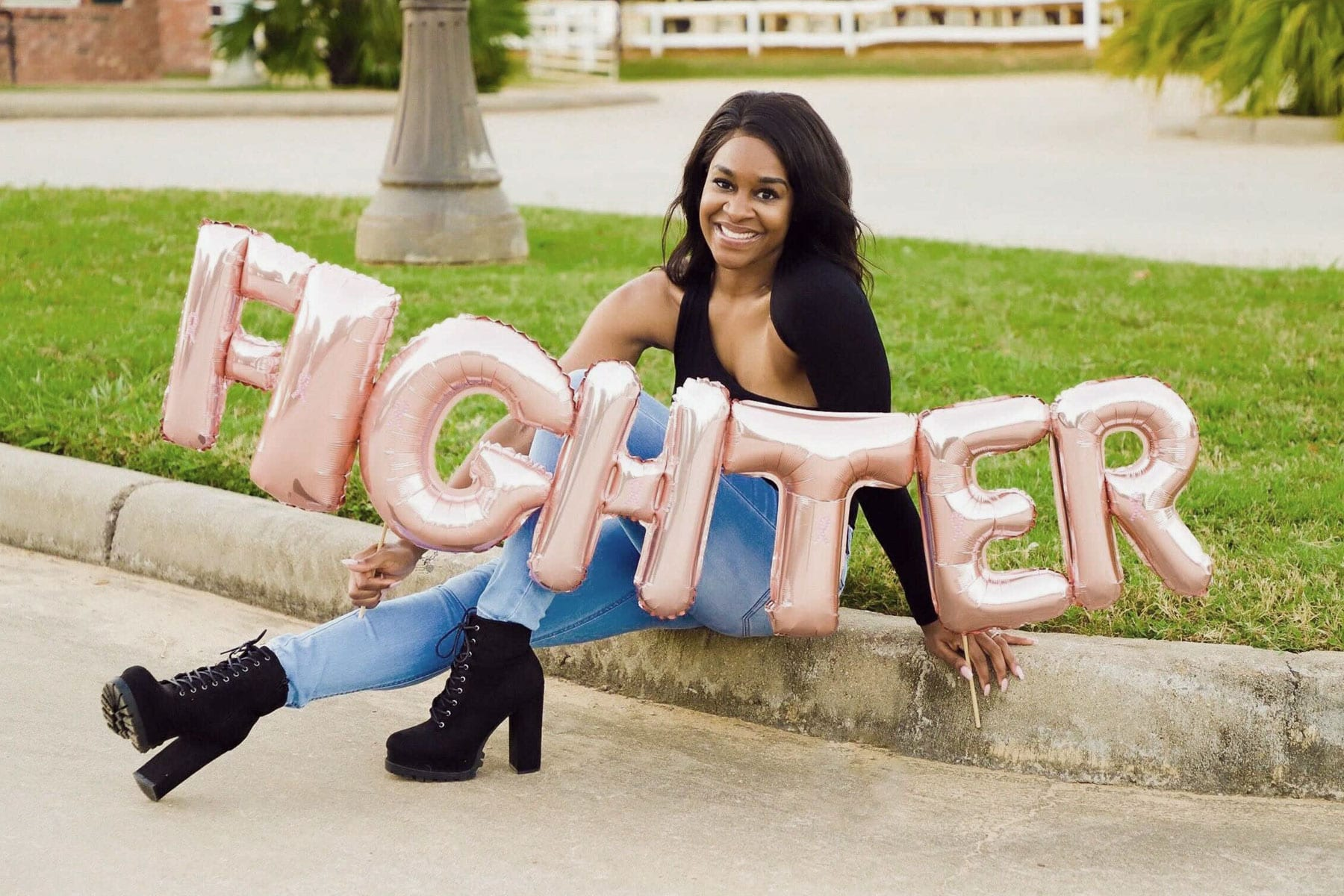 """A woman sits on the ground holding a ballon that reads """"fighter""""."""