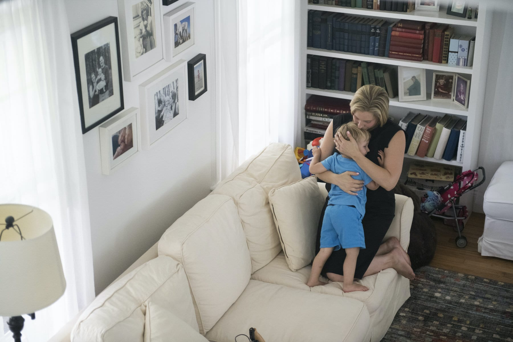 A woman embraces her son while sitting on a couch.
