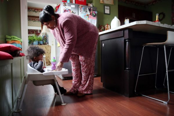 A woman leaning over a child in a high chair.