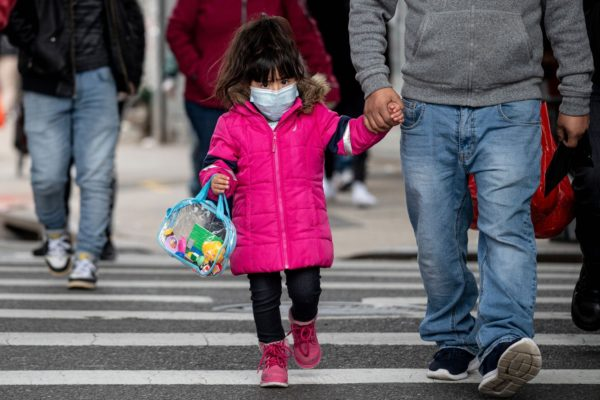 A small girl wearing a mask walks down the street in New York City.