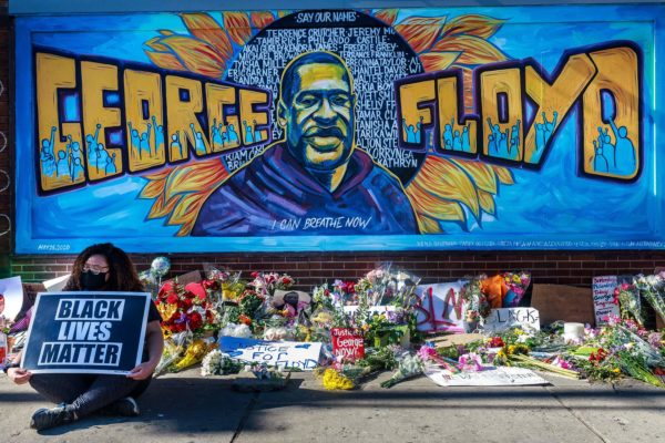 A woman holding a Black Lives Matter sign sitting before a mural of George Floyd, which is serving as a makeshift memorial.