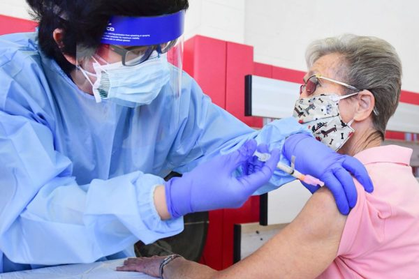 An older woman receives a COVID vaccine from a nurse.
