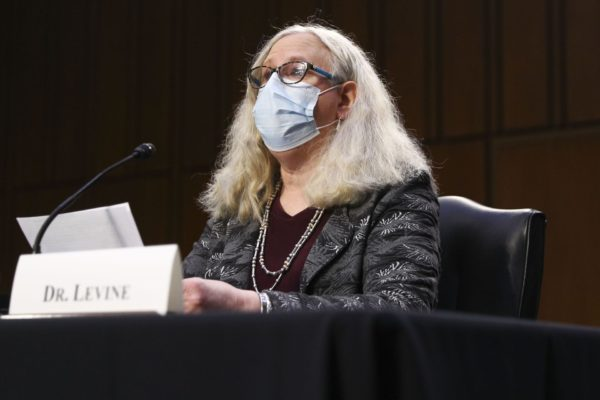 Dr. Rachel Levine speaking at a desk with a mask on.