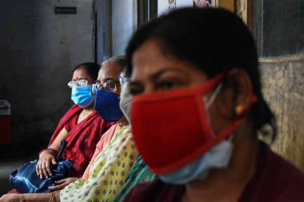 Women are wearing protective masks and waiting outside a covid-19 vaccination center.