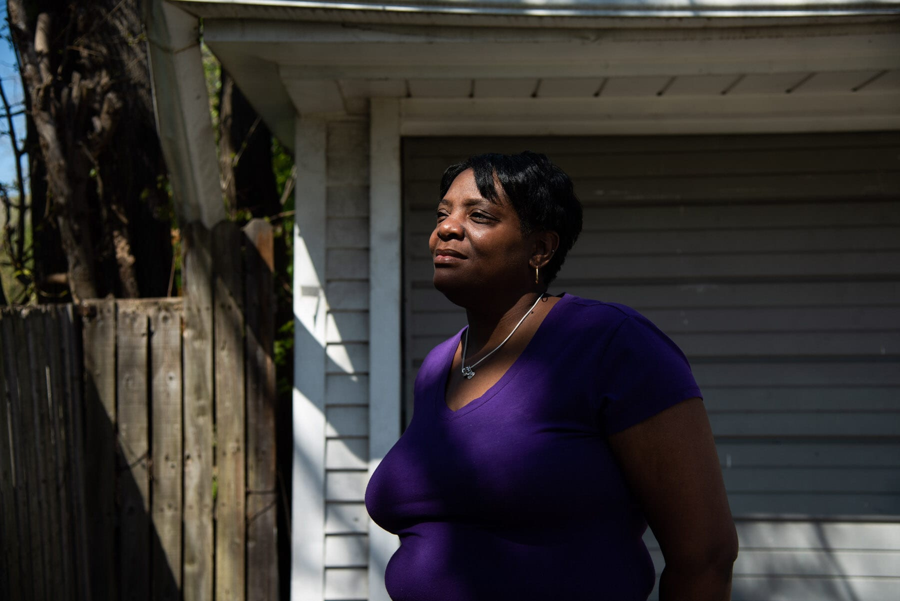 A woman stands in front of her garage.