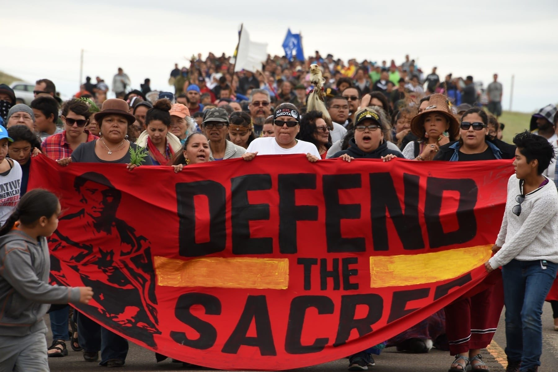 A group of Native American protesters marching with a sign that says