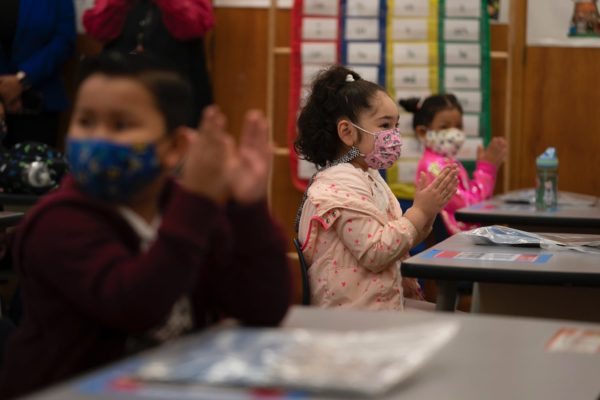 First graders wearing masks applaud in class