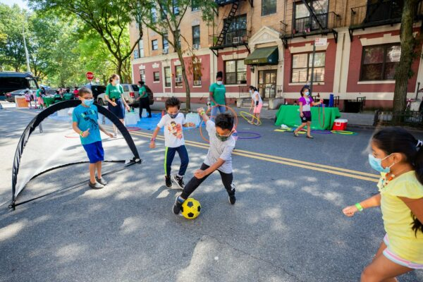 Kids playing soccer on a city street.