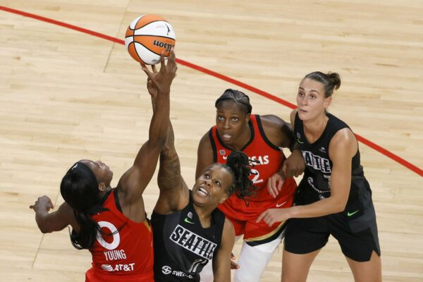 Jackie Young #0 of the Las Vegas Aces and Epiphanny Prince #11 of the Seattle Storm vie for a jump ball as Chelsea Gray #12 of the Aces and Stephanie Talbot #7 of the Storm look on during their game at Michelob ULTRA Arena on June 27, 2021