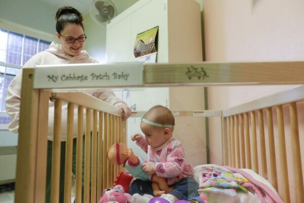 A mother watches over her daughter as she plays in her crib inside her room at a correctional facility.