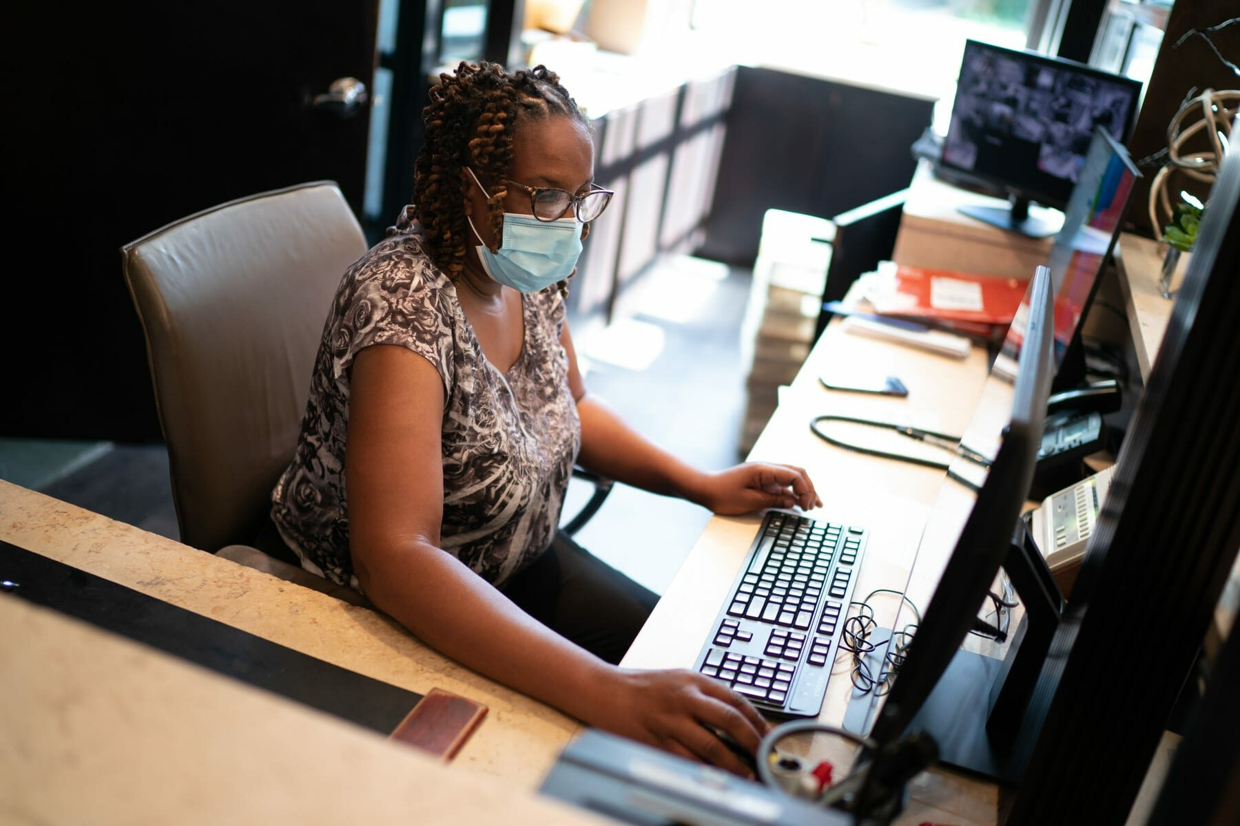 A Black women works behind a desk at an apartment building.