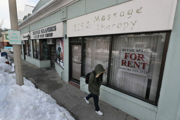 A person walks by an empty massage parlor.