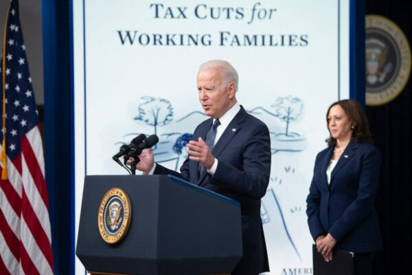 US President Joe Biden, with Vice President Kamala Harris (R), speaks about the Child Tax Credit relief payments.