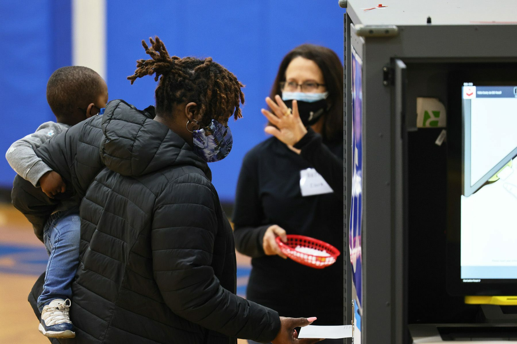 A woman holding a young child casts her vote in the Georgia run-off election at Dunbar Neighborhood Center.
