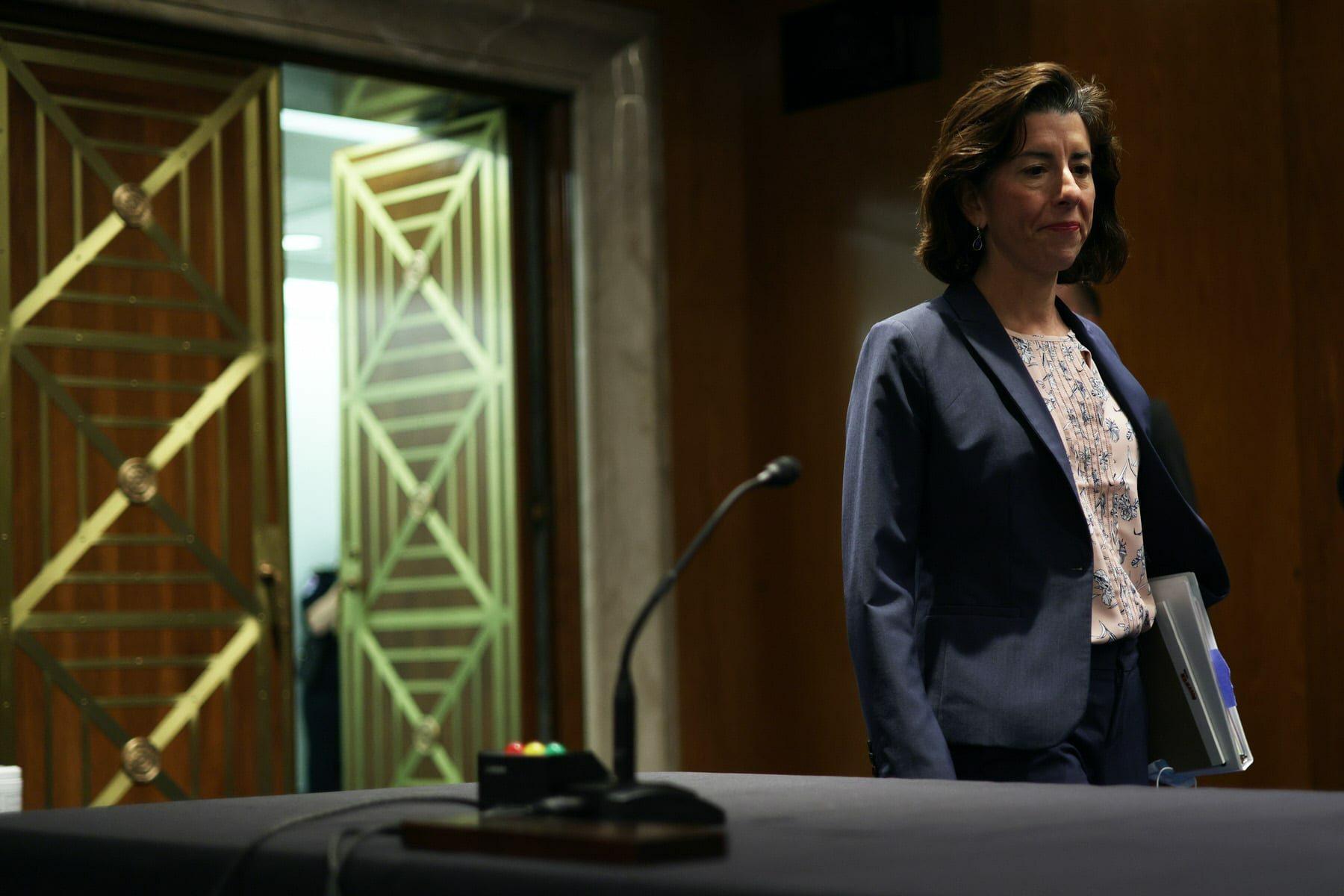 U.S. Secretary of Commerce Gina Raimondo walks into a hearing.
