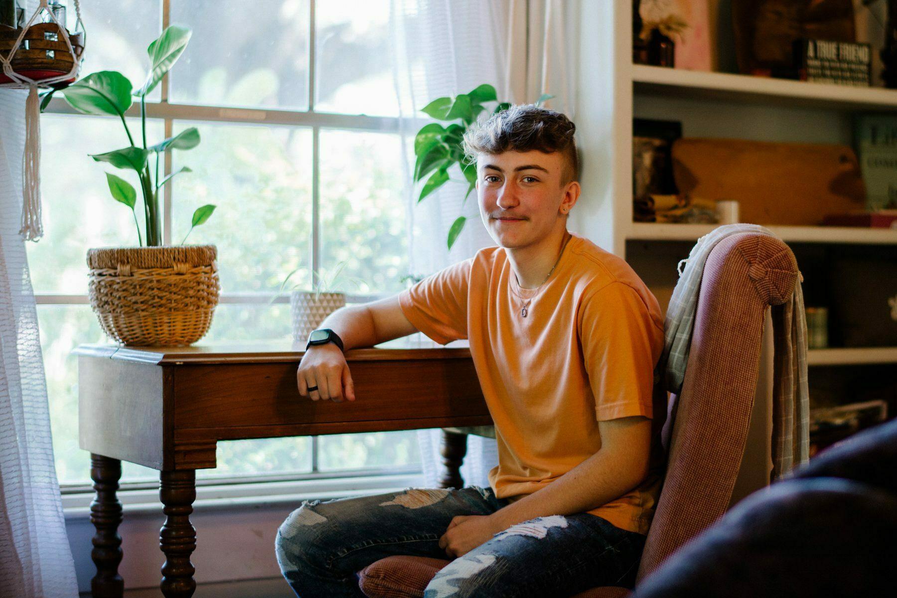 A teenage boy sits at his desk.