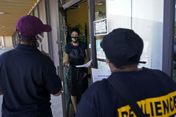 An outreach team goes door to door to educate the community on vaccines.