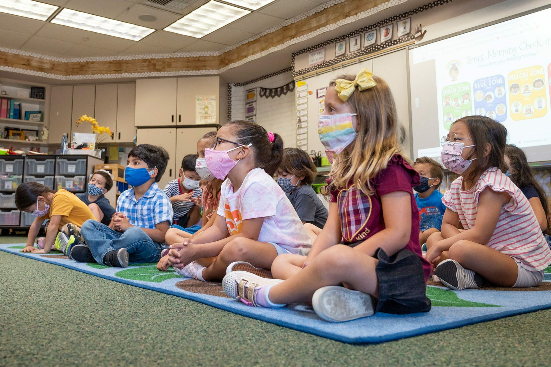 Students listen to their teacher during their first day of kindergarten.
