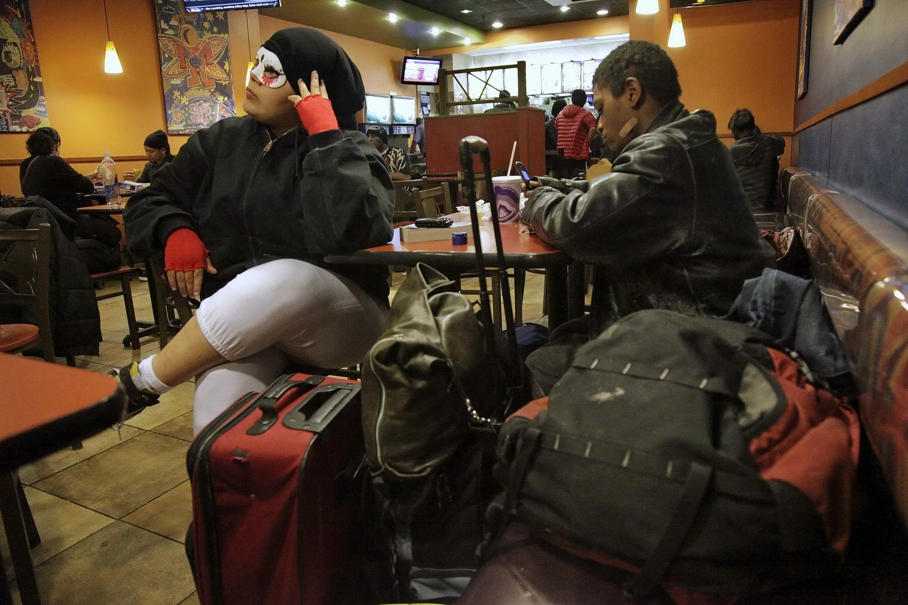 Queer youth sit with their belongings at a table in a fast food restaurant.