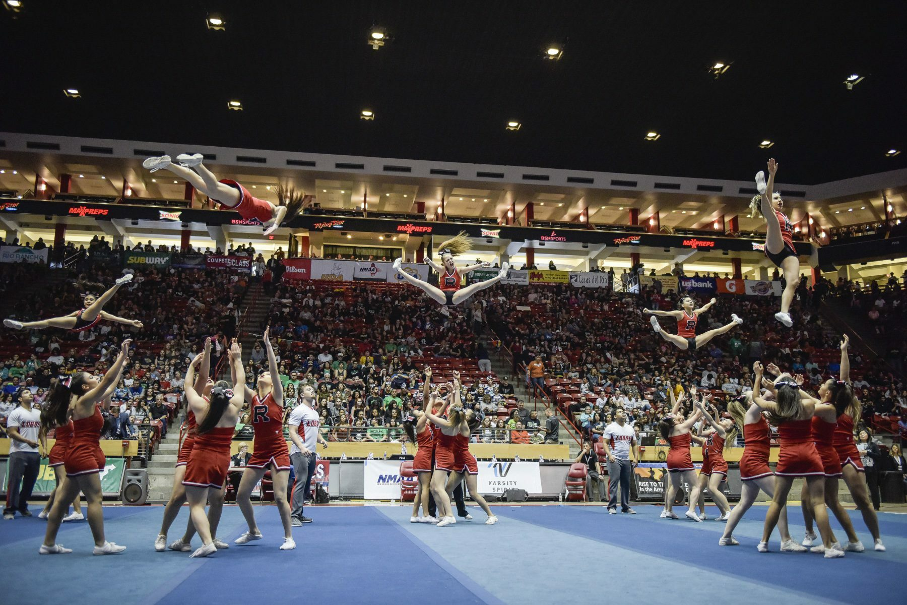 Cheerleaders doing stunts on a competition floor.