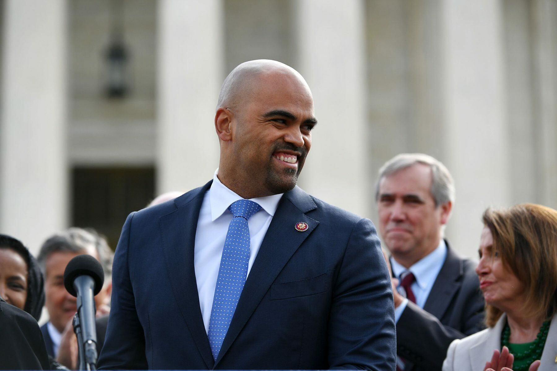 Colin Allred smiling before a microphone.