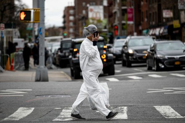 A pregnant woman wearing a hazmat suit and a mask walks in the streets.
