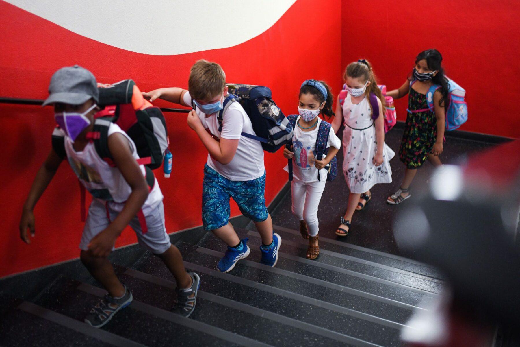 School children wearing masks in a hallway.