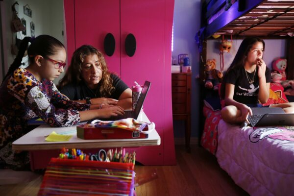 Two girls sit in their room on laptops during remote learning as mom helps.