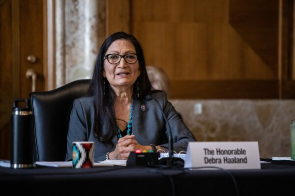 Deb Haaland sitting at a table speaking into a microphone.