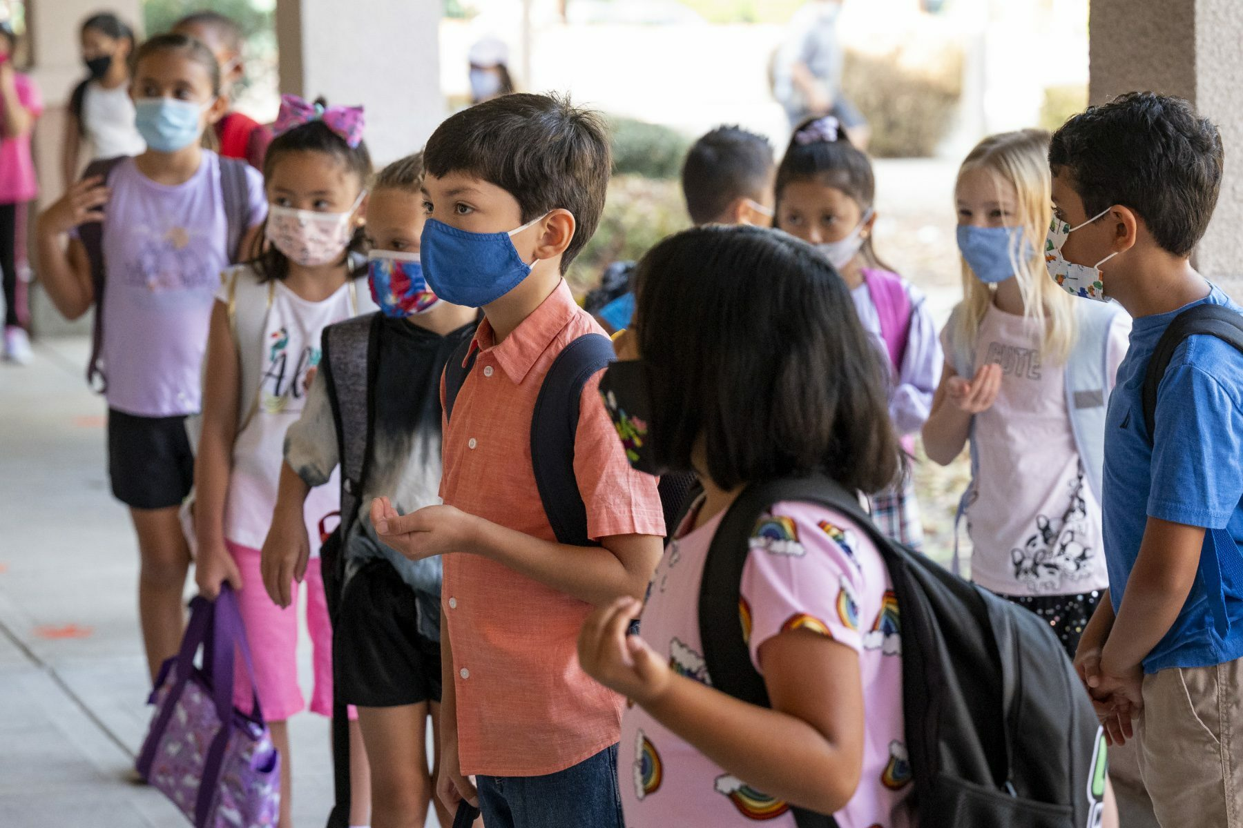 Second grade students stand with masks on.