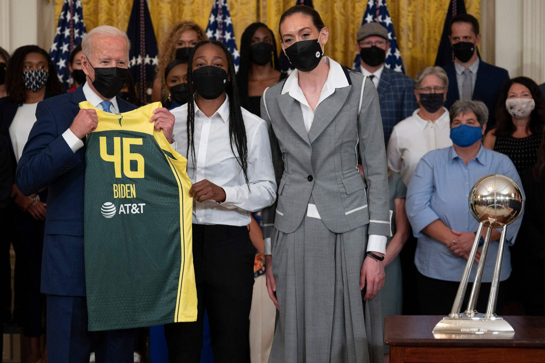 President Biden holding a basketball jersey standing by members of the Seattle Storm.