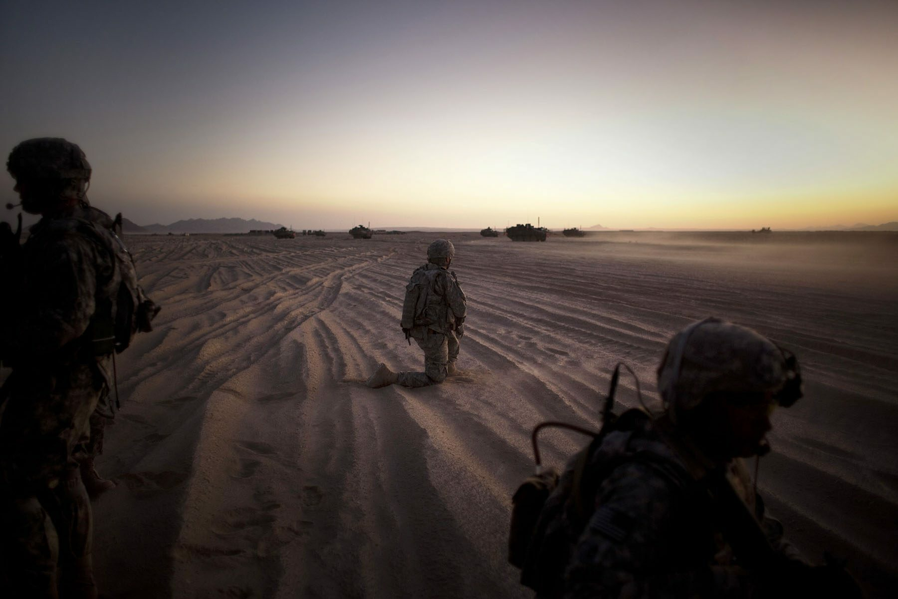 U.S. soldiers kneel in the sand looking at tanks in the distance at sunset.