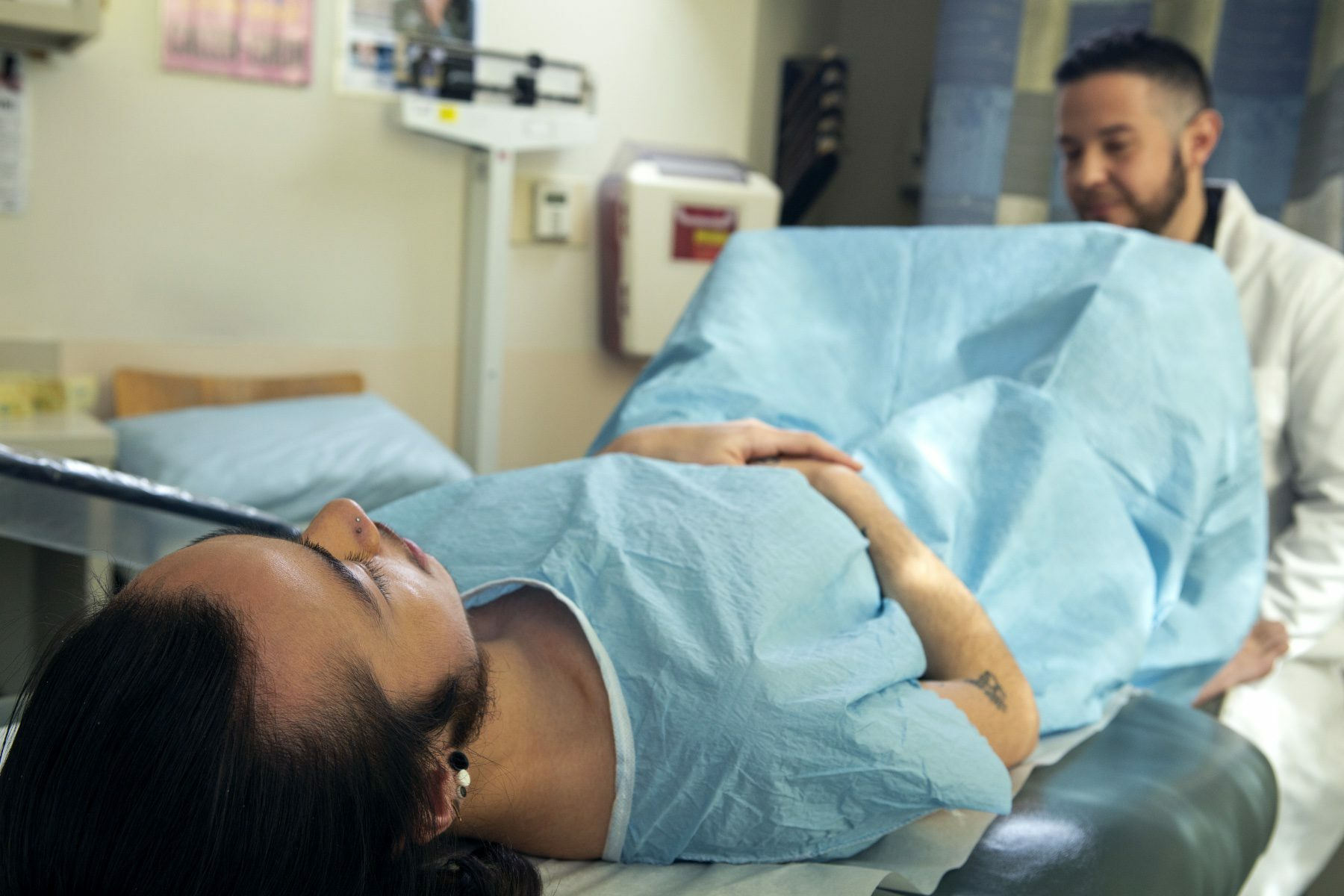 A genderqueer person in a hospital gown receiving a pelvic exam.