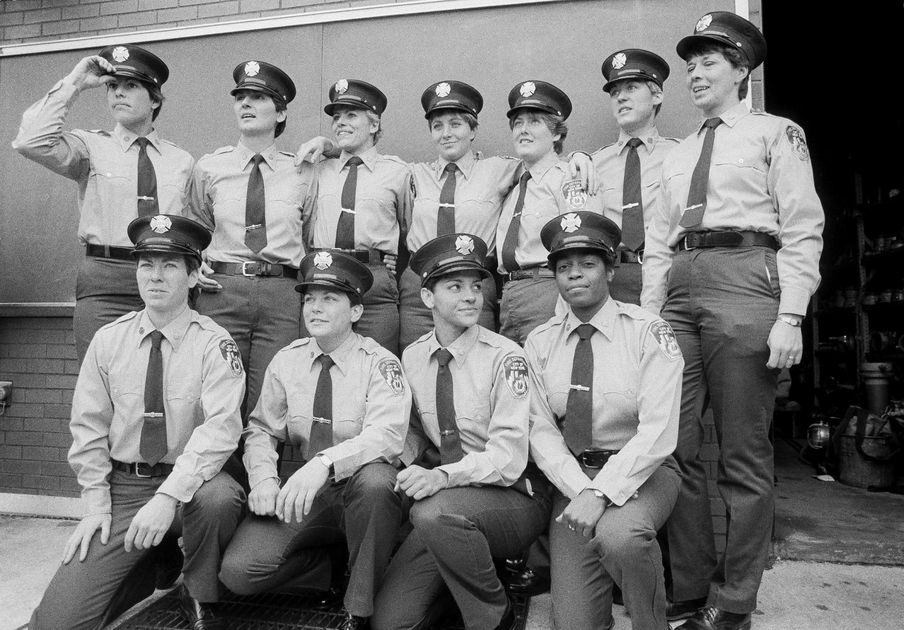 A group of woman firefighters pose in a black and white photo.