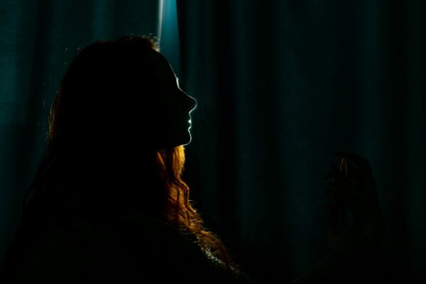 Silhouette of a young woman in the dark.