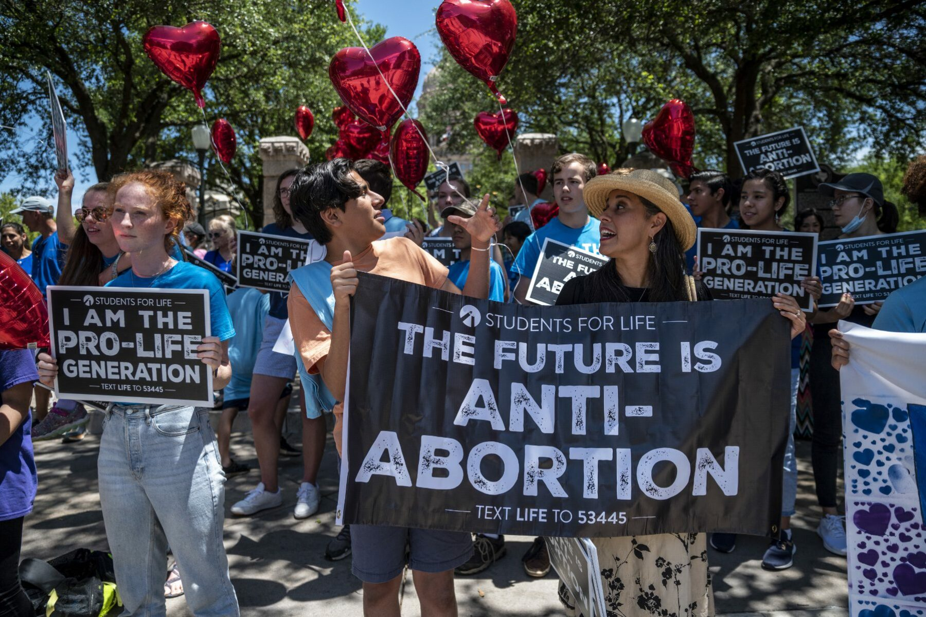 Anti-abortion protesters outside of the Texas Capitol with a sign that reads,