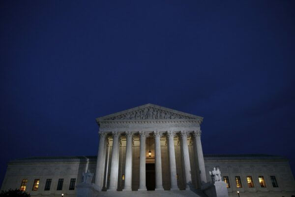 A view of the front of the Supreme Court building at dusk.