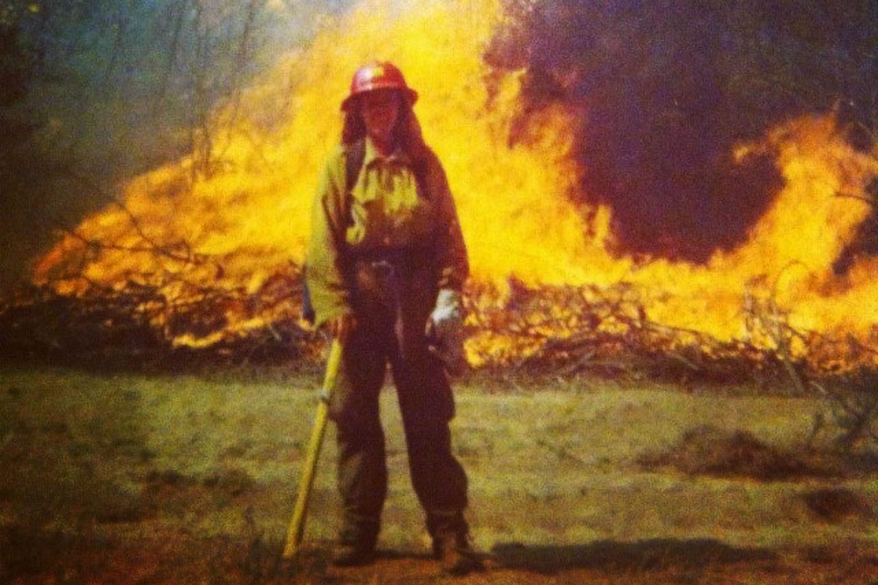 Stacy Selby poses for a photo in front of a fire.