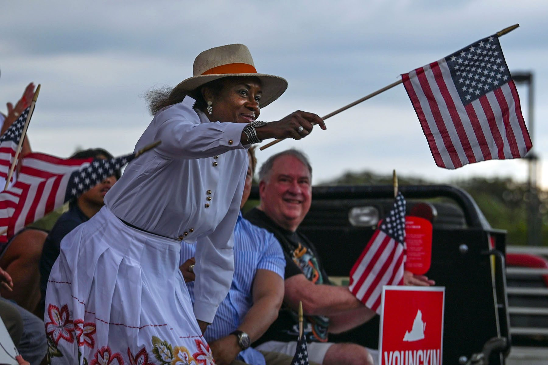 Winsome Sears smiles and waves an American flag at an event.