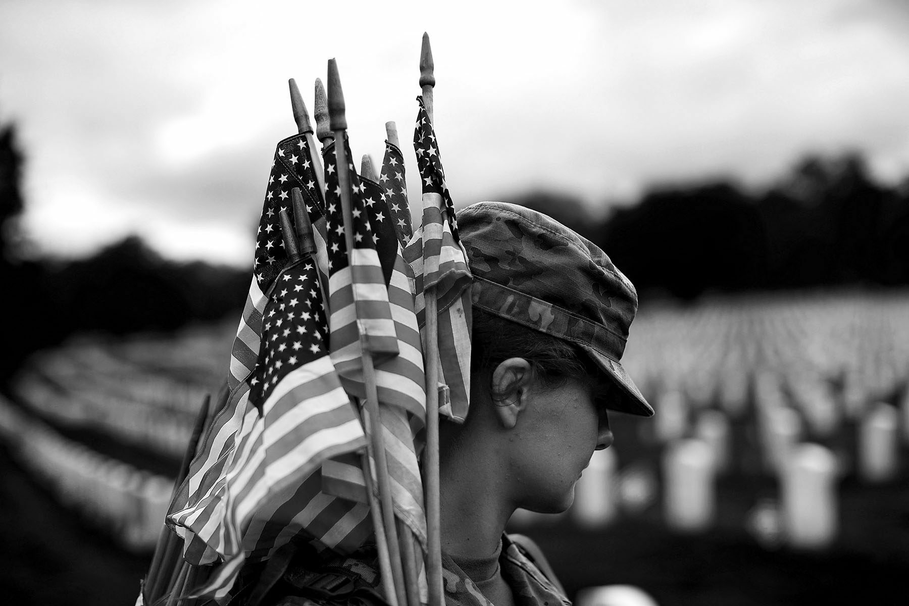 A female soldier holds American flags over her shoulder. Her face is partly obscured by her cap.
