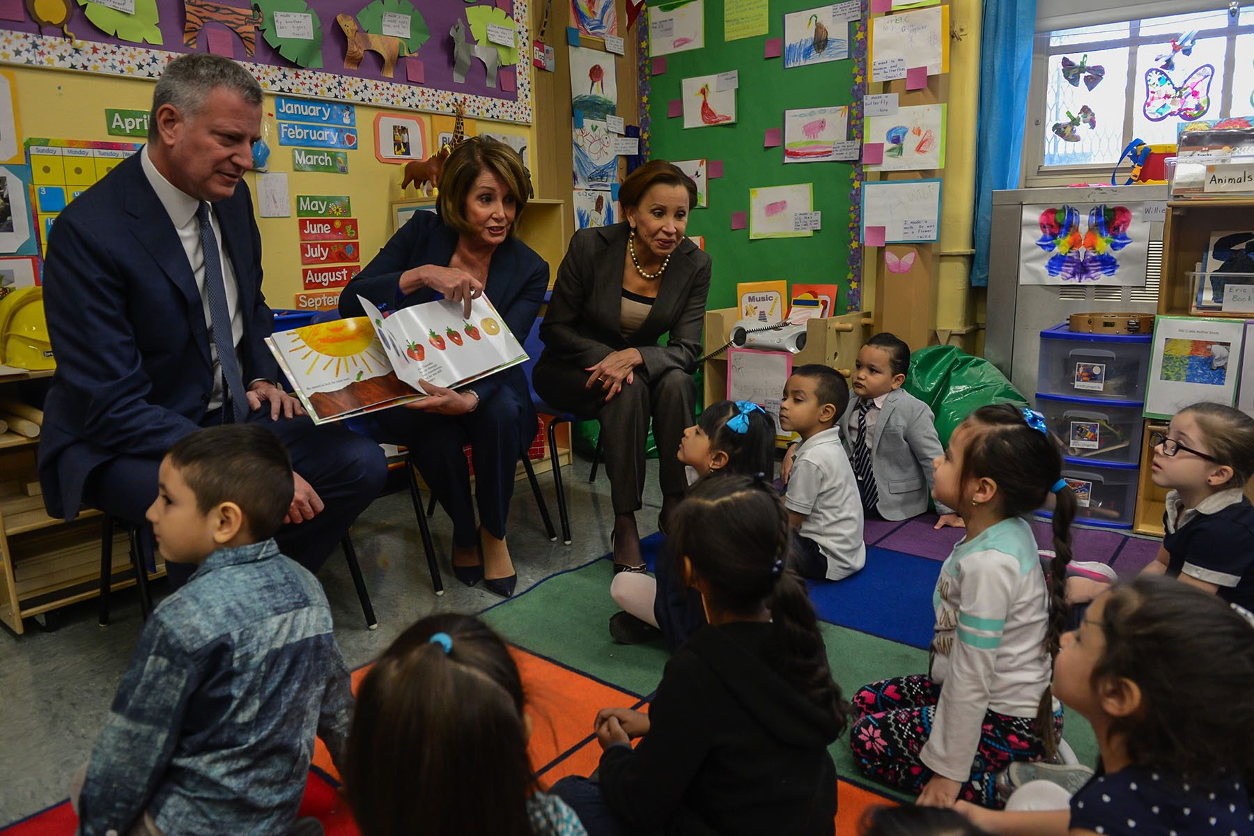 Nancy Pelosi, flanked by Bill DeBlasio and Nydia Velazquez points to a drawing of a strawberry in a children's book while children look on in a colorful classroom.